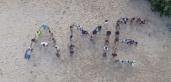 Sigle de l'AME retracé sur la plage avec les élèves